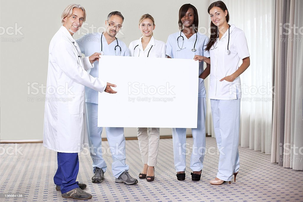 Happy group of doctors holding a blank placard royalty-free stock photo
