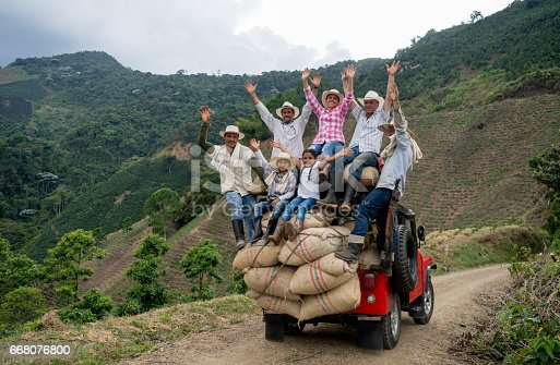Group of happy Colombian farmers transporting coffee on a car and looking at the camera with arms up (Car model is 1954)