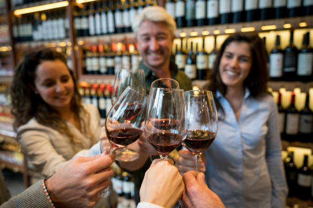 Happy group of friends at a winery tasting red wine and toasting stock photo