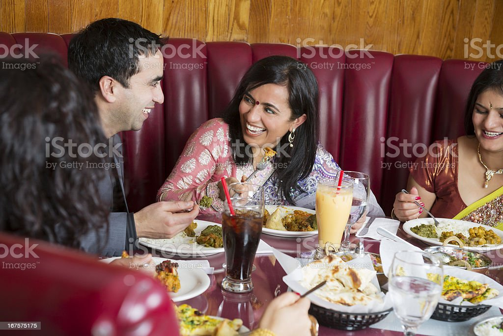 Happy group of friends at an indian restaurant royalty-free stock photo