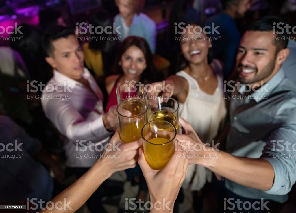 Happy group of friends at the nightclub making a toast Portrait of a happy group of friends at the nightclub making a toast at the dance floor - lifestyle concepts 30-39 Years Stock Photo