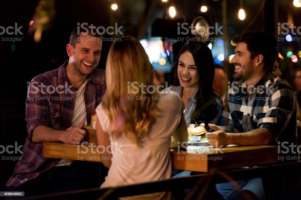 Happy group of friends eating at a restaurant stock photo