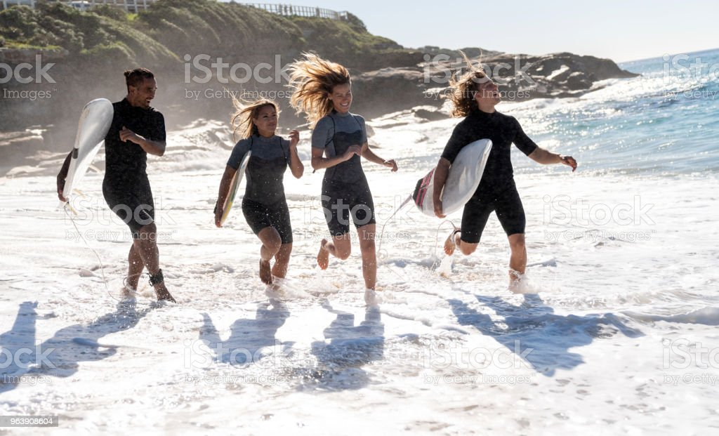 Happy group of friends having fun surfing at the beach - Royalty-free Adult Stock Photo