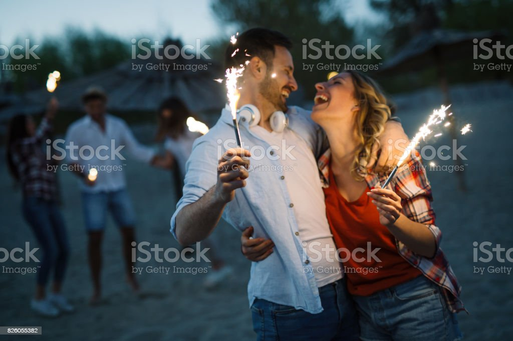 Happy group of friends lighting sparklers and enjoying freedom stock photo