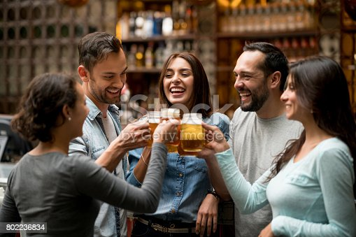 istock Happy group of friends making a toast at a restaurant 802236834