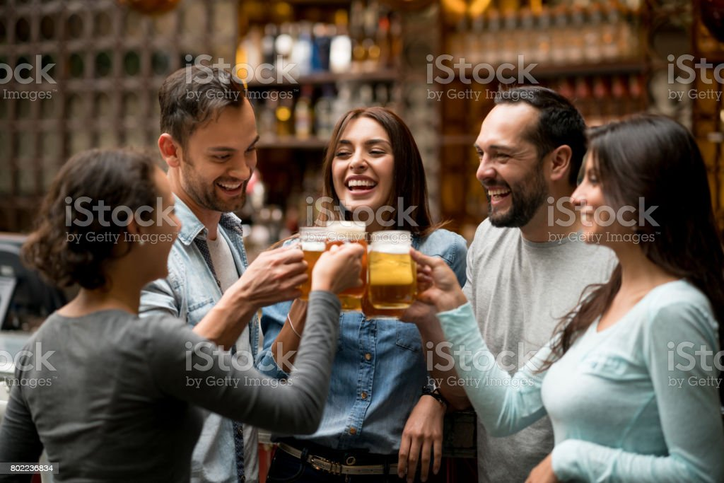 Happy group of friends making a toast at a restaurant stock photo