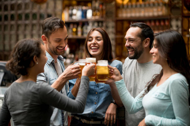 happy group of friends making a toast at a restaurant - beer alcohol stock pictures, royalty-free photos & images