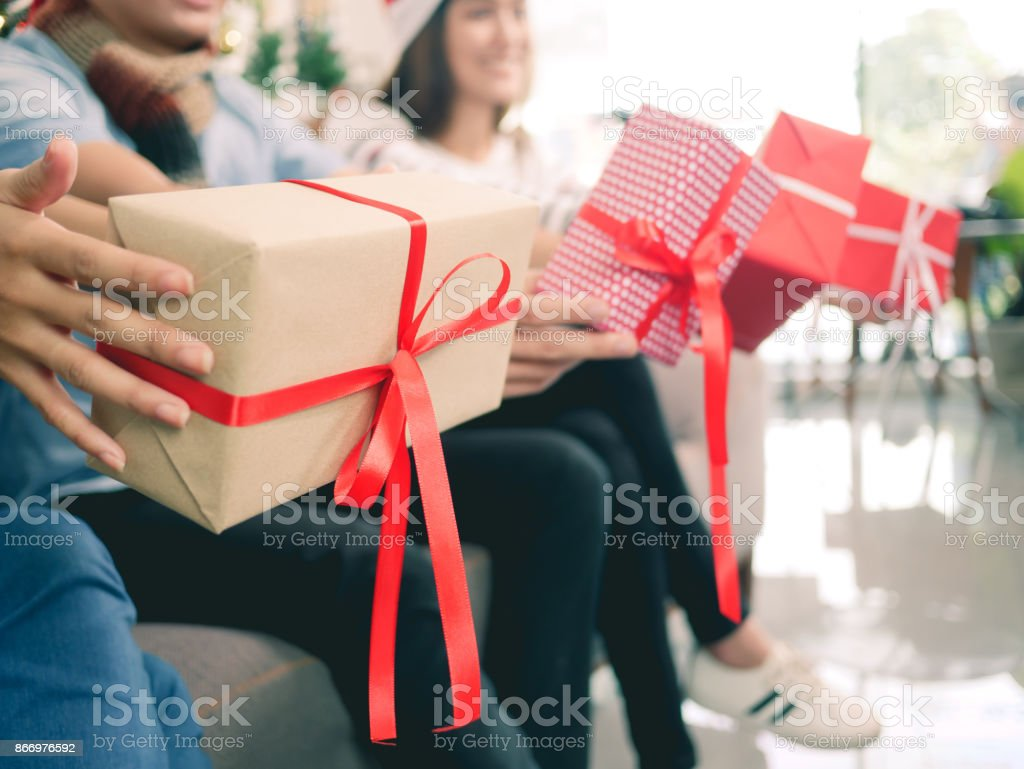 happy group of friends party christmas exchange gift box, close-up man and girl hands holding gift box. stock photo