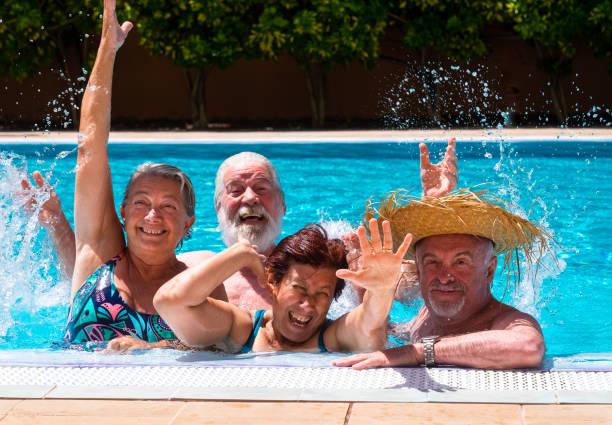 glückliche gruppe von freunden spielen genießen das schwimmbad zusammen. helles sonnenlicht und transparentes wasser. großes lächeln und arme überstreckt - senior bilder wasser stock-fotos und bilder