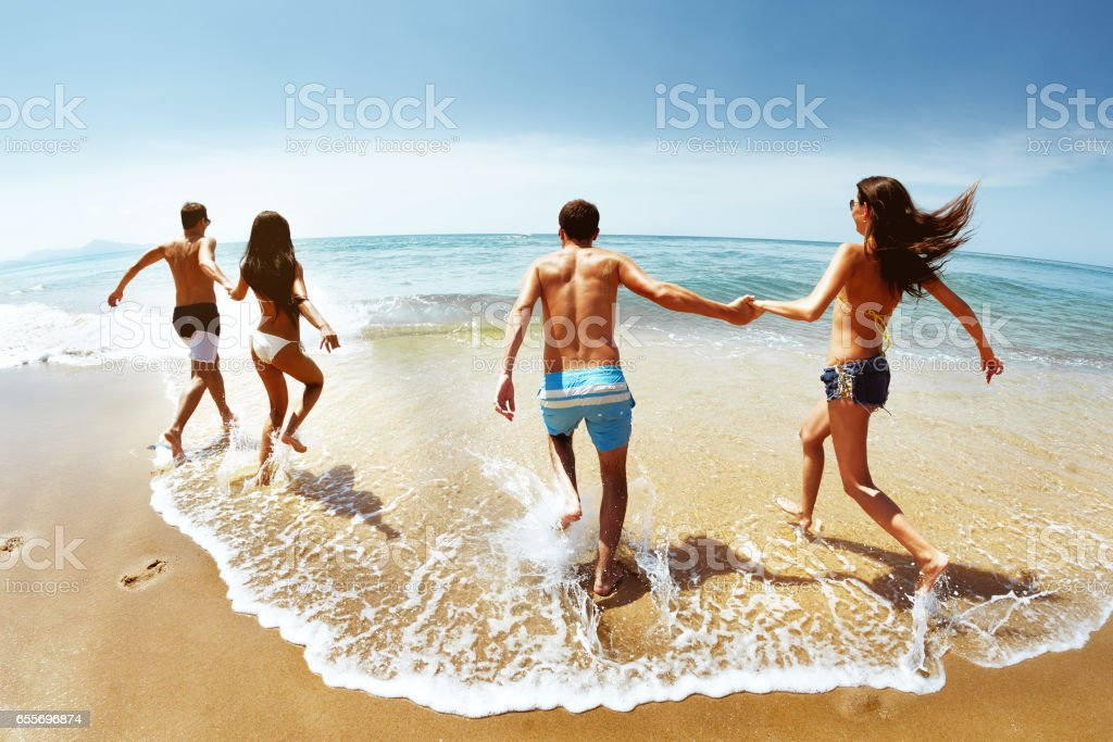 Happy group of friends runs to sea stock photo