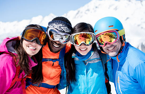 Happy group of friends skiing Happy group of friends skiing and looking at the camera smiling and wearing goggles ski goggles stock pictures, royalty-free photos & images