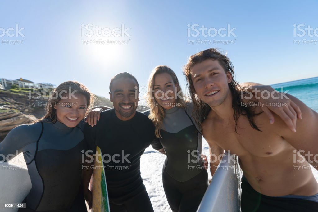 Happy group of friends surfing at the beach - Royalty-free Adult Stock Photo