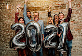 istock Happy group of friends with face mask celebrating new 2021 year - Confetti falling in the air - Young people with balloons in hands making new year party at home - Focus on balloons. 1287216087