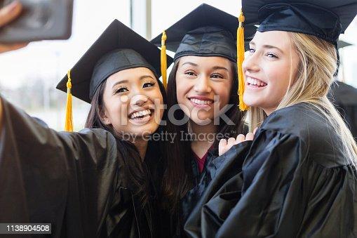 Excited high school girls pose for selfie together after graduation.