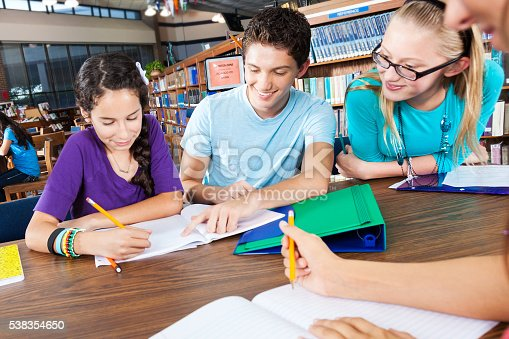 Diverse group of friends work together on homework at the library. They have papers and pencils in hand.