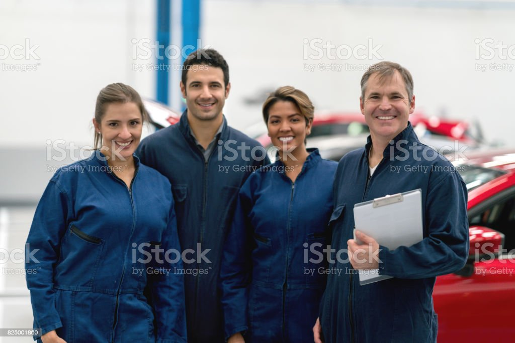Happy group of mechanics working at an auto repair shop stock photo