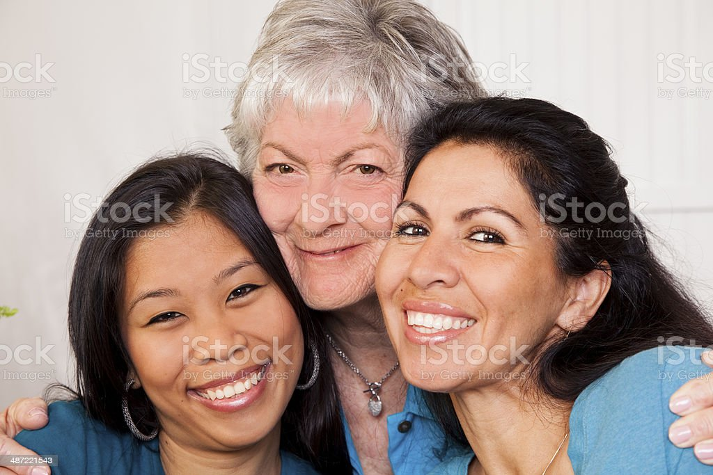 Happy group of mixed age, diverse women hugging. stock photo