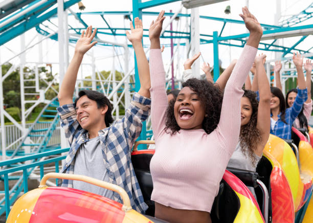 happy group of people having fun in a rollercoaster at an amusement park - roller coaster stock pictures, royalty-free photos & images