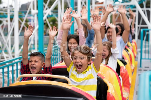 Happy group of people having fun in an amusement park riding on a rollercoaster with arms up and screaming - lifestyle concepts