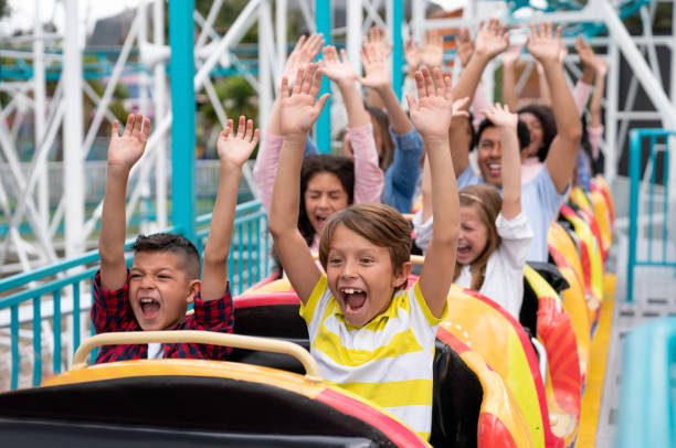 Happy group of people having fun in a rollercoaster at an amusement park Happy group of people having fun in an amusement park riding on a rollercoaster with arms up and screaming - lifestyle concepts amusement park stock pictures, royalty-free photos & images