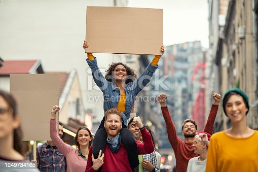 Group of multiethnic people on city street holding blank cardboard placard celebrating victory during a protest. Young group of content men and smiling women marching through a city. People protesting on road with empty sign.