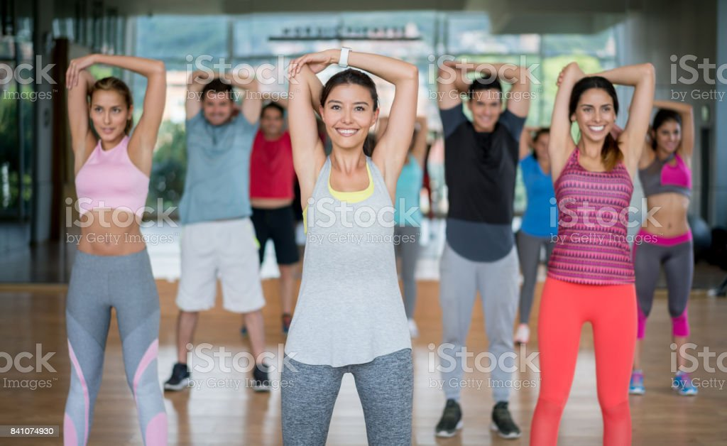 Happy group of Latin American people in a stretching class at the gym...