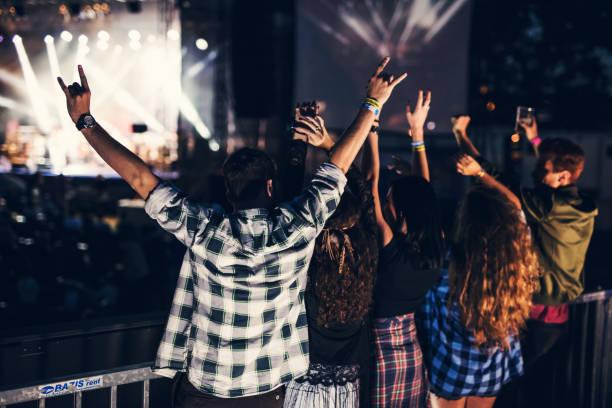 glückliche gruppe von menschen springen und tanzen beim musikfestival. ansicht von hinten - tanz camp stock-fotos und bilder