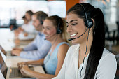 Group of people working at a call center wearing headsets and looking happy - communications concepts