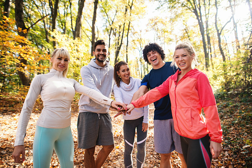 Happy group of runners smiling and stacking hands while standing in woods in autumn.