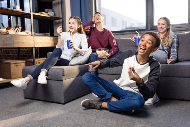 glückliche gruppe von teenagern film zusammen zu hause jugendliche spaß konzept - jugendfilm stock-fotos und bilder