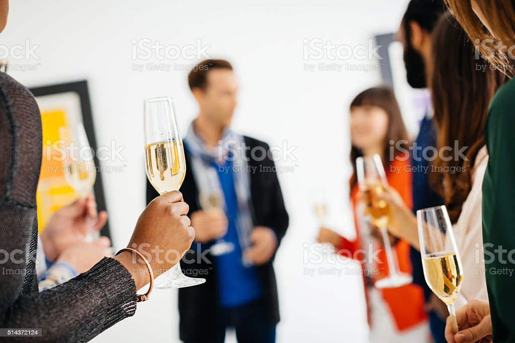 Happy group of young people celebrating a gallery opening stock photo