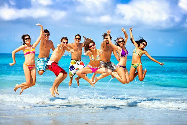 Felice gruppo di giovani saltare su una festa in spiaggia - foto stock