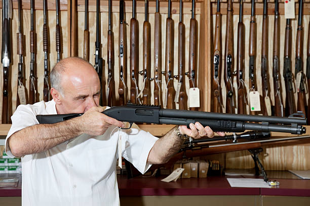 Happy Gun Store Owner Mature gun shop merchant with rifle aiming gun shop stock pictures, royalty-free photos & images