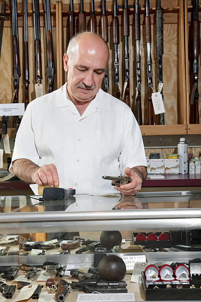Happy Gun Store Owner Mature male merchant at gun shop with credit card reader gun shop stock pictures, royalty-free photos & images