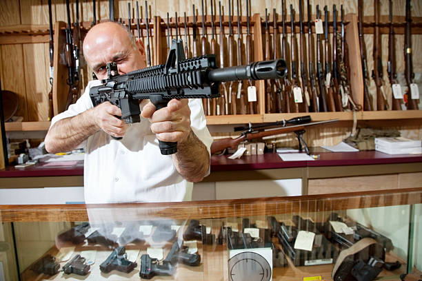 Happy Gun Store Owner Mature merchant aiming with rifle in gun shop gun shop stock pictures, royalty-free photos & images