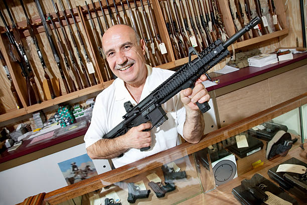 Happy Gun Store Owner Portrait of a happy mature merchant with rifle in gun shop gun shop stock pictures, royalty-free photos & images