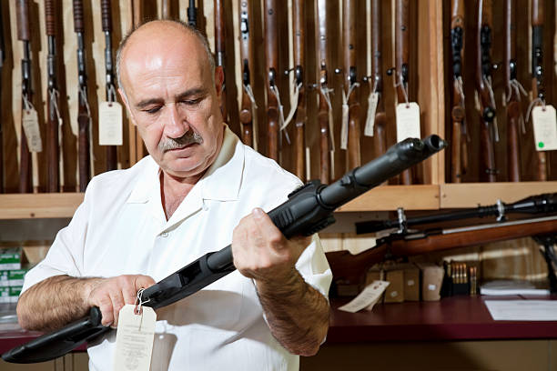 Happy Gun Store Owner Mature gun shop merchant looking at rifle in store gun shop stock pictures, royalty-free photos & images