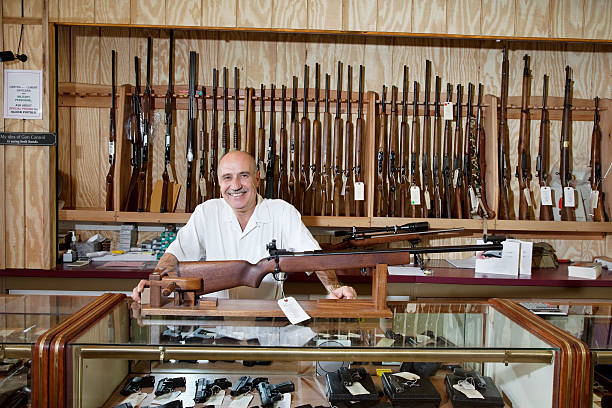 Happy Gun Store Owner Portrait of a happy weapon shop owner gun shop stock pictures, royalty-free photos & images