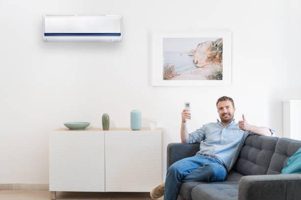 Happy guy cool down using air conditioning at home stock photo