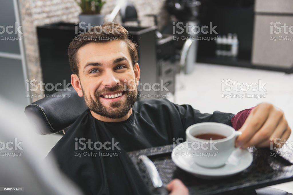 Happy guy drinking beverage at beauty salon stock photo