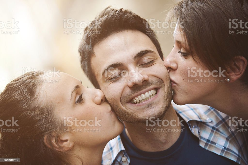 Happy guy gets a kiss from two girls stock photo
