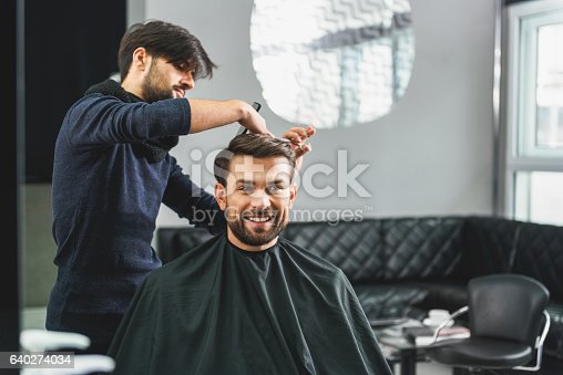 986804130istockphoto Happy guy getting haircut by hairdresser 640274034