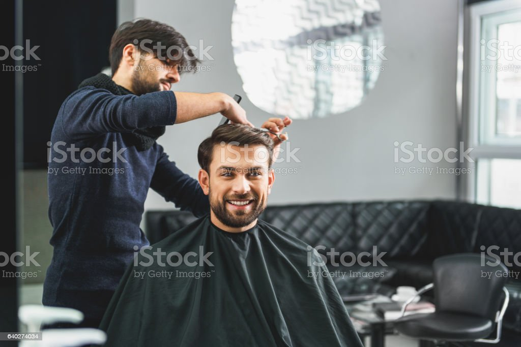 Happy guy getting haircut by hairdresser stock photo