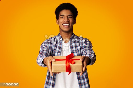 istock Happy Guy Offering Craft Gift Box to Camera 1159063560
