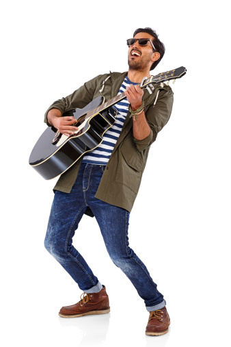 Full length portrait of a happy guy playing a guitar over white background