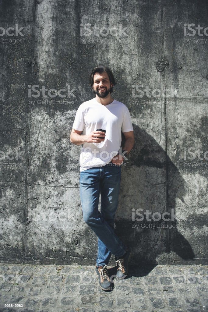 Happy guy standing in the sun with drink - Royalty-free Adult Stock Photo