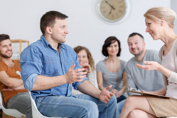 Happy guy talking to therapist Happy guy sitting facing a female therapist, talking and listening to advice in group psychotherapy drug rehab stock pictures, royalty-free photos & images
