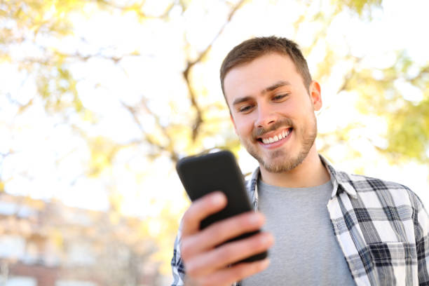 Happy guy uses a smart phone in a park stock photo