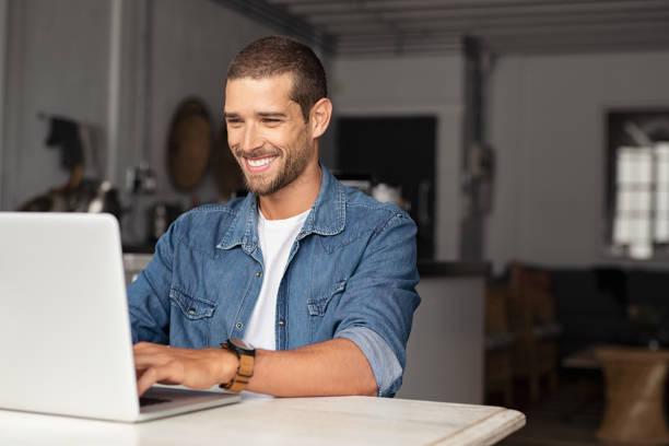 Type heureux utilisant l'ordinateur portatif - Photo