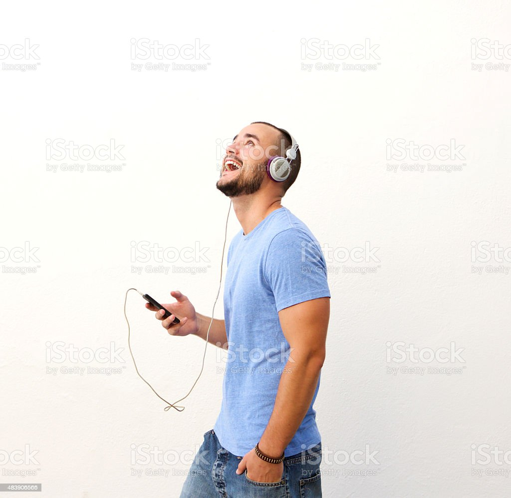 Happy guy walking with cell phone and headphones stock photo